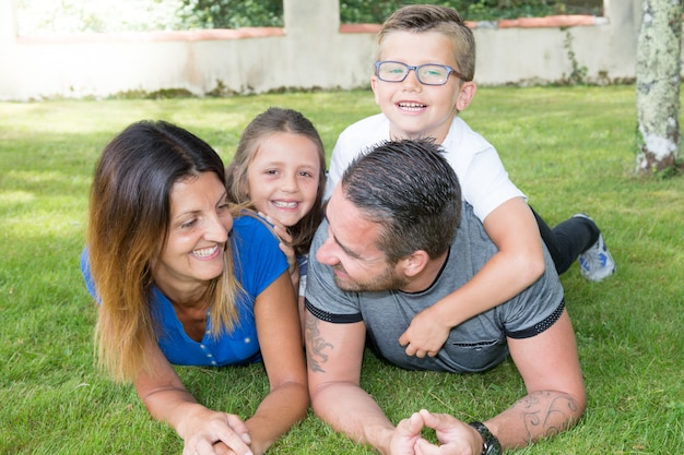 Cheerful family of four lying on green home garden