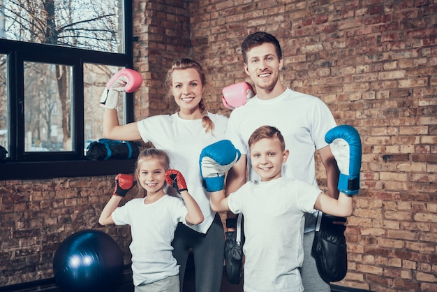 Cheerful family in the gym in boxing equipment.