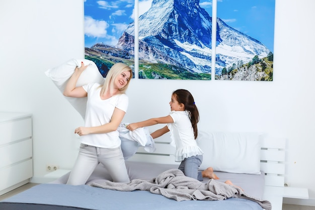 Cheerful family having pillow fight in a bedroom