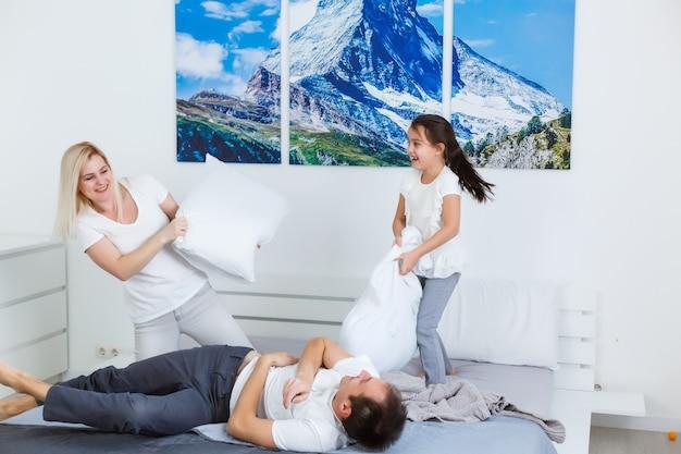 Веселая семья борется подушками в спальне