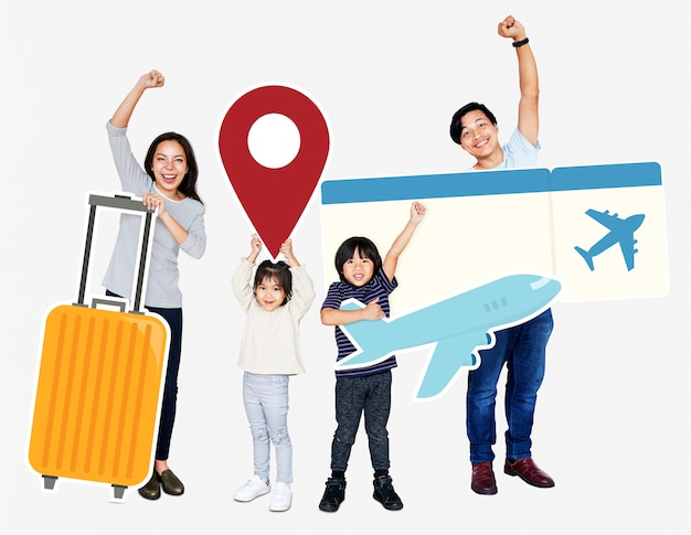 Cheerful family holding travel icons and ticket
