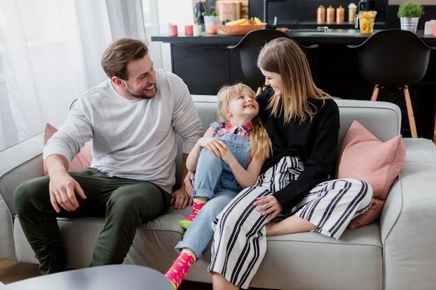 ソファで抱き合っている陽気な家族