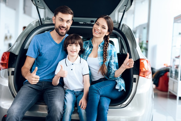 Cheerful family is smiling while sitting in the trunk.