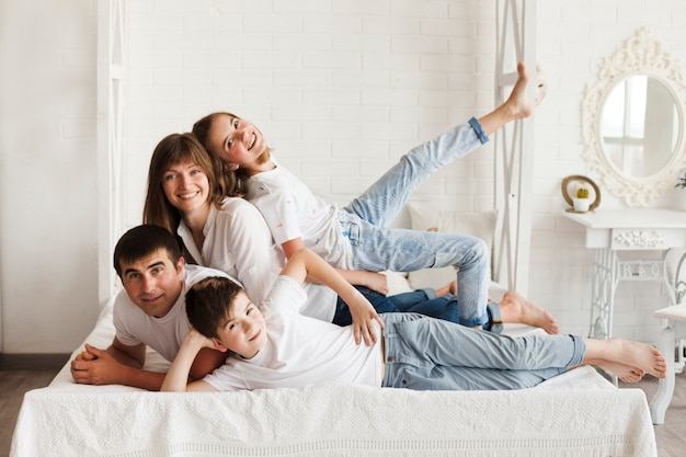 Cheerful family lying on bed looking at camera