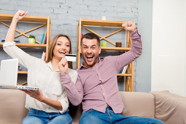 Веселая семья делает покупки в интернете с ноутбуком и банковской картой