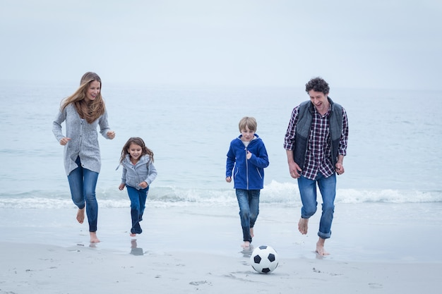 Cheerful family playing soccer at sea shore against sky