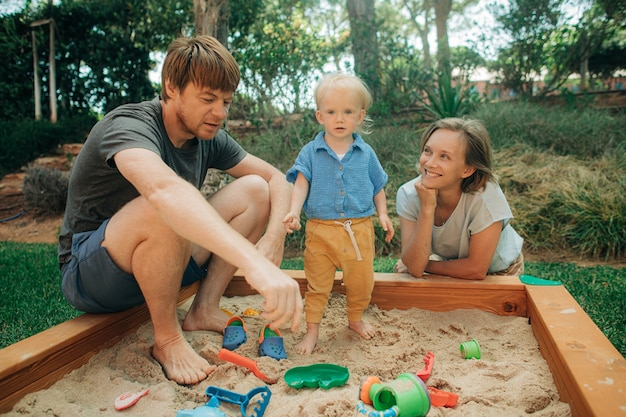Cheerful family playing together in sandpit