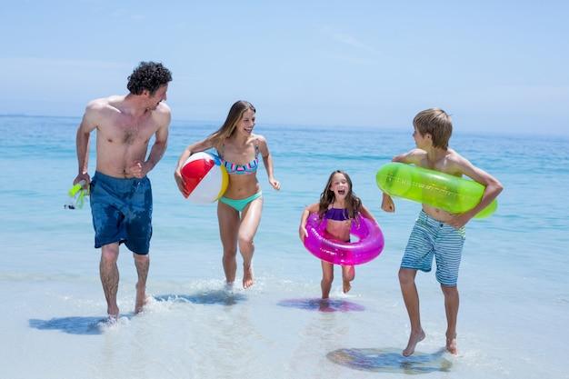 水泳用具と浅い水の中を実行している陽気な家族