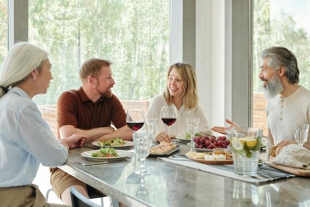 컨트리 하우스의 한 테이블에 앉아 저녁 식사를하는 쾌활한 가족