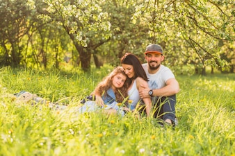 Cheerful family sitting in green grass during summer