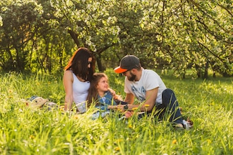 Cheerful family sitting on grass in green park