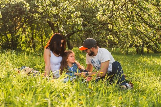Веселая семья сидит на траве в зеленом парке