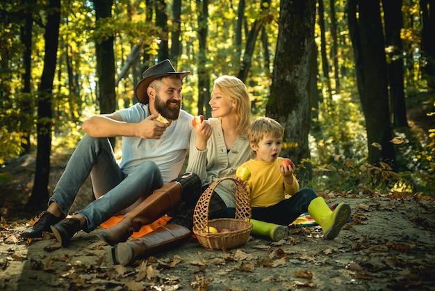 公園でのピクニック中に芝生に座っている陽気な家族若い笑顔の家族がピクニックをしています...