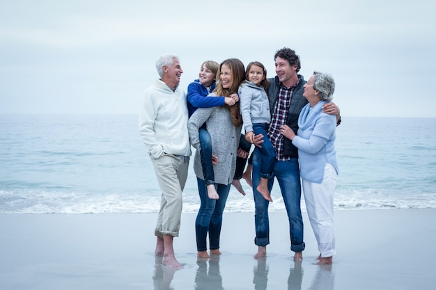 Cheerful family standing at sea shore against sky