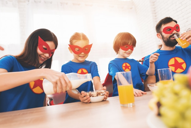 Cheerful family in superhero costumes decided to eat.