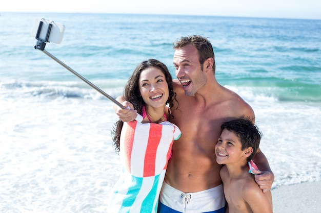 Cheerful family taking selfie at sea shore
