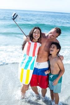 Веселая семья, делающая селфи, стоя на мелководье
