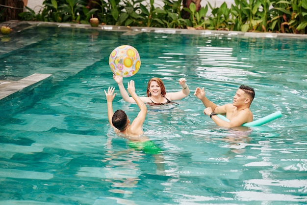 Cheerful family of three throwing inflatable ball to each other when playing in swimming pool of spa resort
