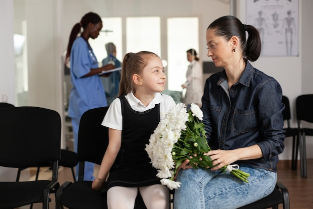 Famiglia allegra in attesa nell'area del corridoio dell'ospedale durante la visita medica