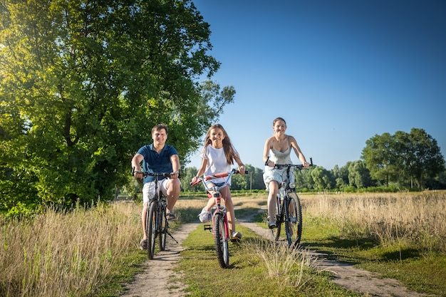 Cheerful family with daughter riding bicycles in meadow at sunny day