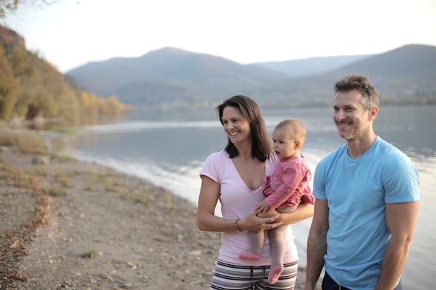 Famiglia allegra con un bambino piccolo in piedi vicino a un lago circondato da colline sotto la luce del sole