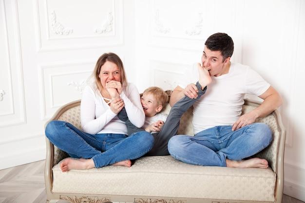 Веселая семья с сыном, играя на светлом фоне