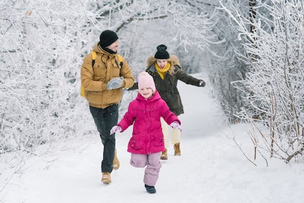 Cheerful family in the woods playing snowballs