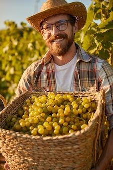 新鮮なブドウのバスケットを持つ陽気な農家
