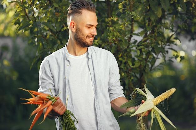 Allegro contadino con verdure biologiche in giardino. verdura biologica mista nelle mani dell'uomo.