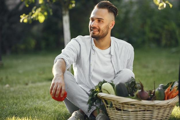 庭で有機野菜と陽気な農家。籐のかごの中の混合有機野菜。
