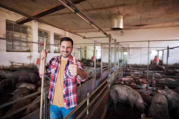 Веселый фермер с вилами стоит в загоне для свиней и заботится о домашних животных свиньях