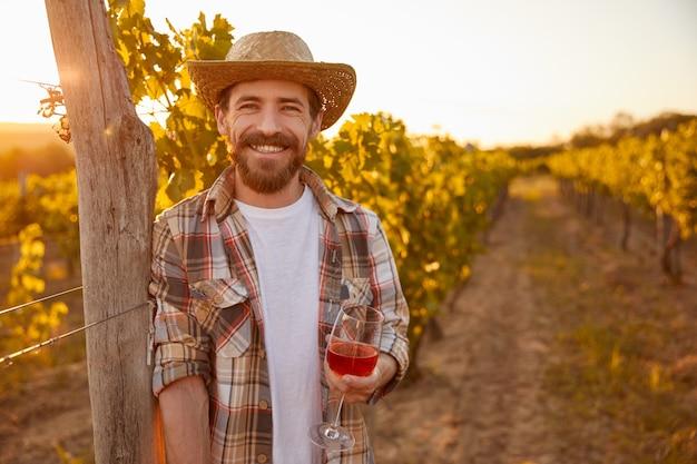 Cheerful farmer with wine resting on vineyard