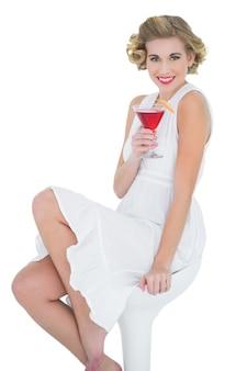 Cheerful fashion blonde model enjoying a cocktail