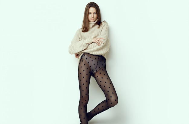 Cheerful fashion hipster girl in cozy sweater and black tights