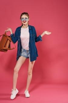 ファッションをポーズする手で陽気なファッション学生バックパック