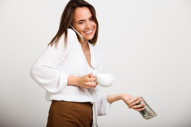 陽気なファッションの女性、コーヒーを飲み、お金を保持し、電話を話す