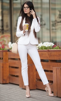 Cheerful fashionable brunette girl holding coffee cup outdoors in city street. woman in the street drinking morning coffee. coffee on the go. beautiful young woman while walking. woman talk on phone.