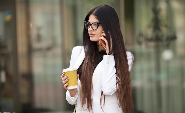 街で屋外のコーヒーカップを保持している陽気なファッショナブルなブルネットの少女。朝のコーヒーを飲みながら通りの若い女性。外出先でコーヒー。歩きながら美しい若い女性。女性は電話で話します。