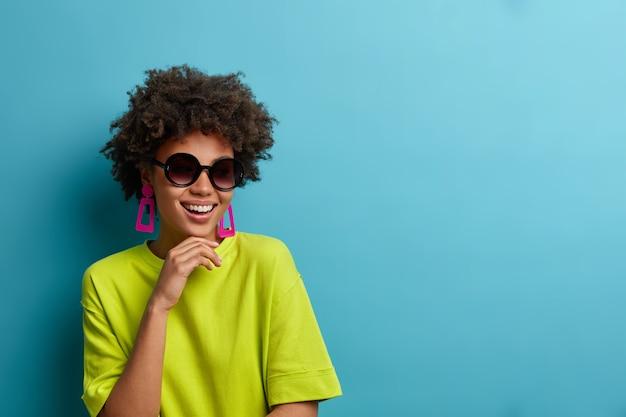 La donna etnica riccia alla moda allegra tiene il mento, indossa occhiali da sole alla moda e maglietta verde, ha un umore estivo felice, posa per la copertina di una rivista, isolato sulla parete blu con spazio di copia da parte