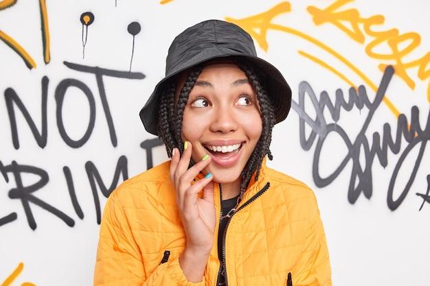 쾌활한 유행 여성 젊은이 미소는 행복하게 옆으로 보이는 세련된 옷을 입고 도시 장소에서 자유 시간을 보내고 다채로운 낙서 벽에 포즈를 취합니다.