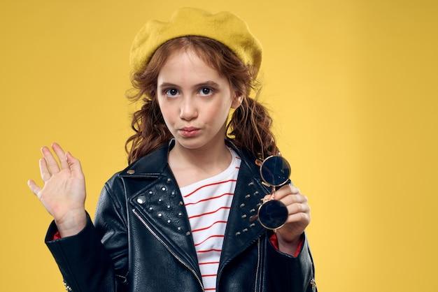 陽気なファッショナブルな女の子の黒いジャケットは、黄色の背景をトリミングしました。高品質の写真