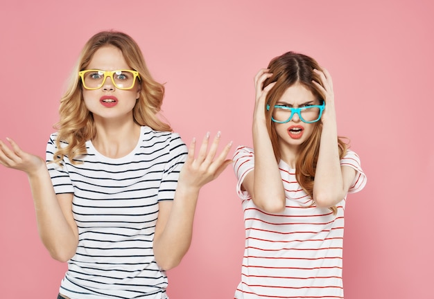 Cheerful fashionable girlfriends in striped tshirts posing pink background