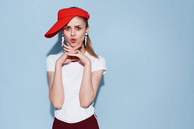 Cheerful fashionable woman in red cap summer clothes posing blue background