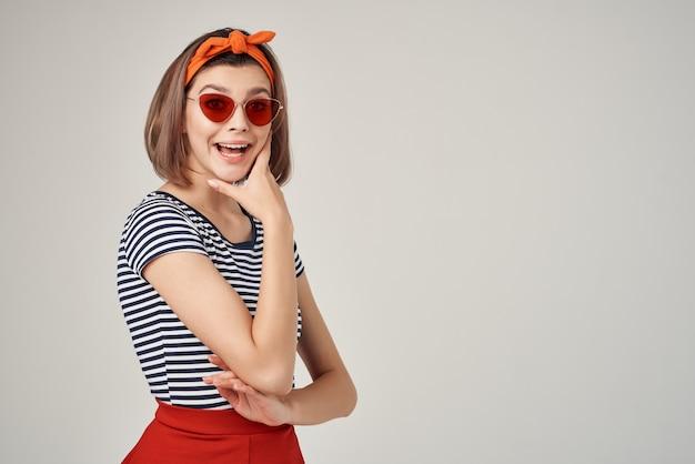 Веселая модная женщина в солнцезащитных очках рука возле лица изолированный фон
