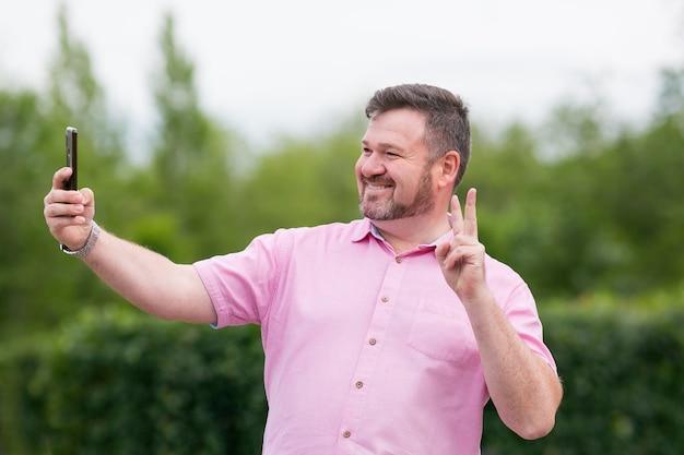 あごひげを生やした陽気な太った男が公園でスマートフォンの自分撮り自撮りで自分の写真を撮る