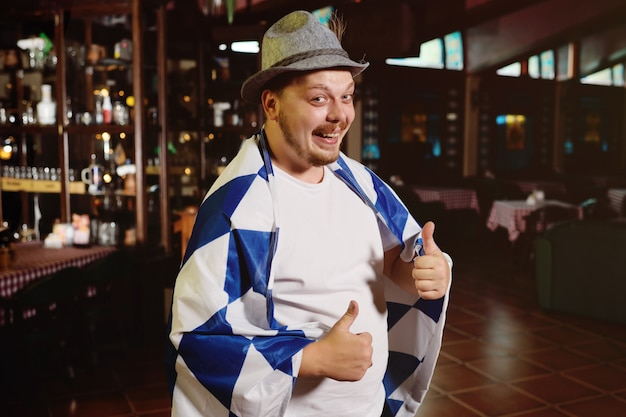Cheerful fat man with a big belly with an oktoberfest flag and a bavarian hat on a pub background