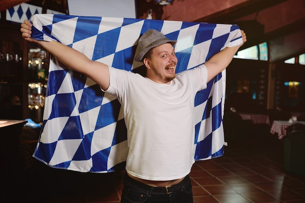 Cheerful fat man with a big belly with an oktoberfest flag and a bavarian hat
