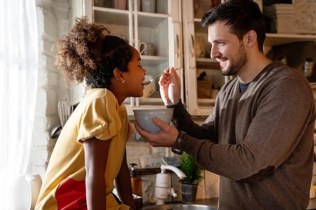 쾌활한 아버지와 그의 흑인 딸이 부엌에서 함께 아침을 먹고 있다