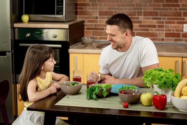 Веселый отец и его дочь вместе завтракают на кухне, разговаривают, веселятся