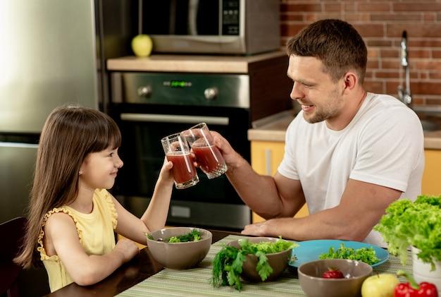 Веселый отец и его дочь завтракают вместе на кухне, разговаривают, держат в руках стаканы сока